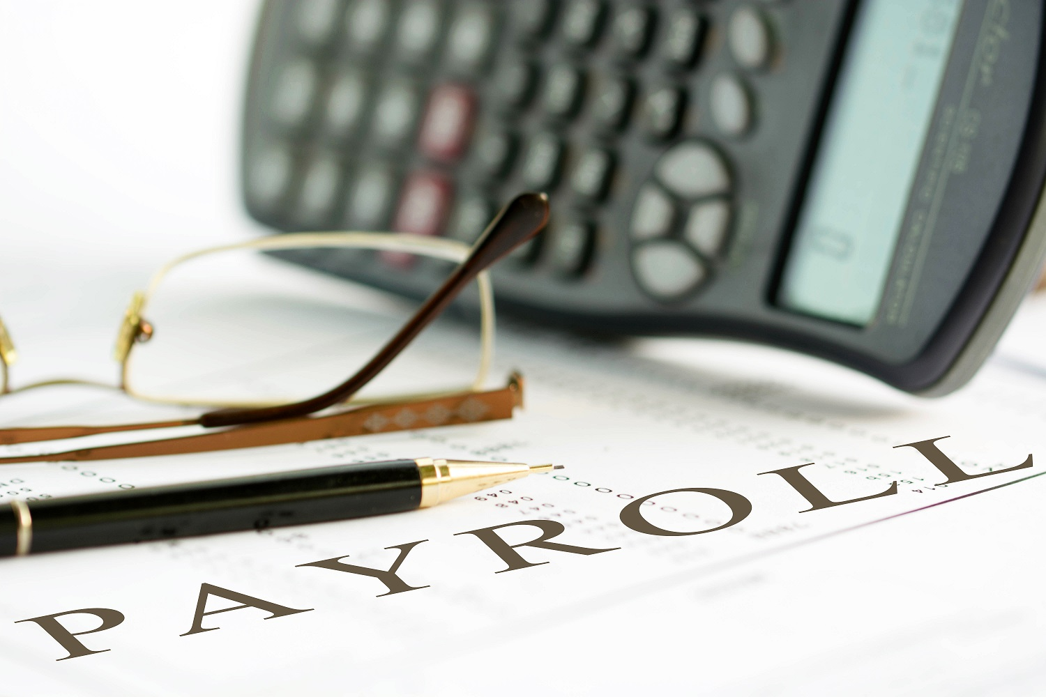 Payroll concept image of a pen, calculator and reading glasses on financial documents.