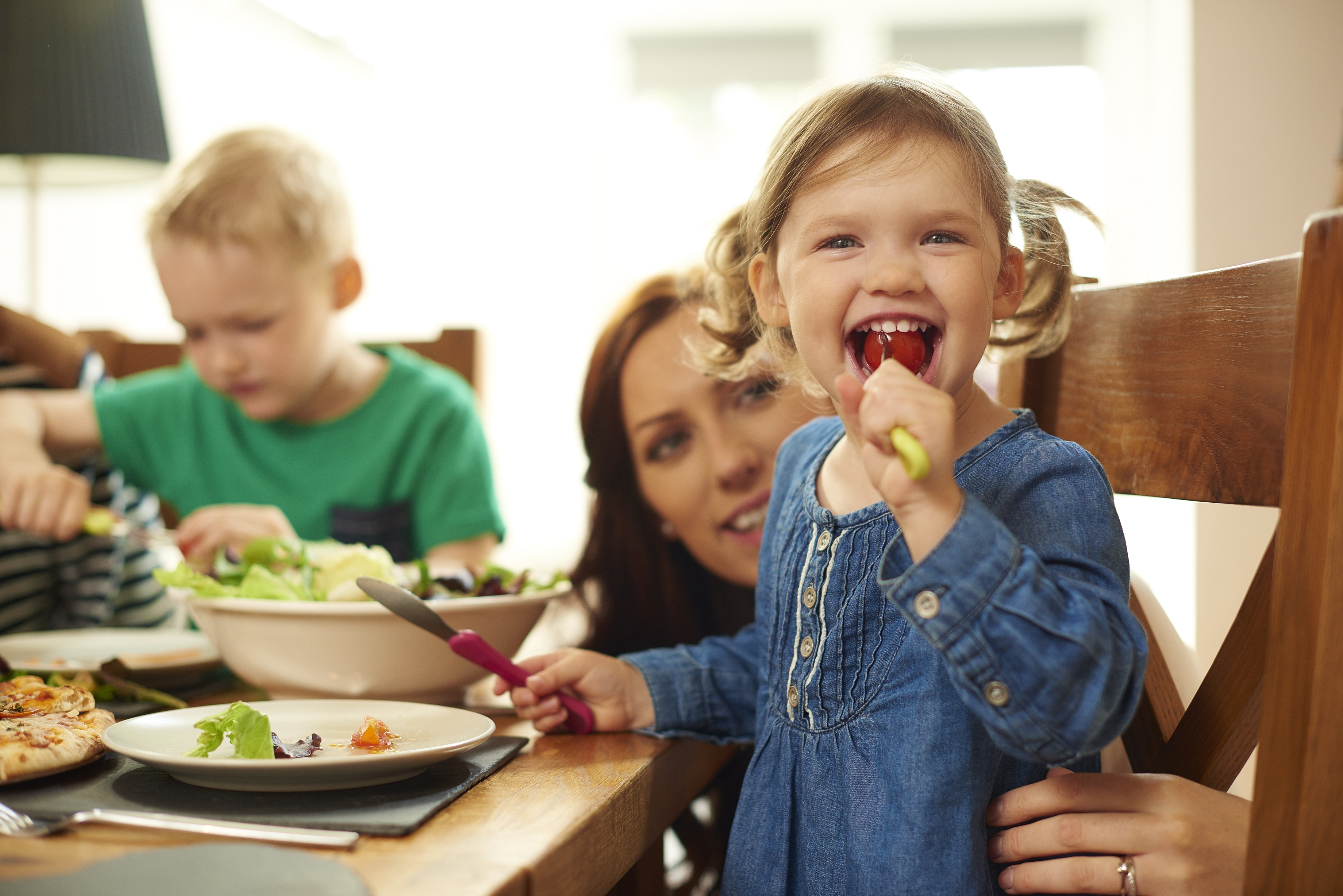 a young family of four sit at the dining table and eat pizza and salad.Mum helps her little girl with her meal , as she cheekily stuffs a whole tomato into her mouth .