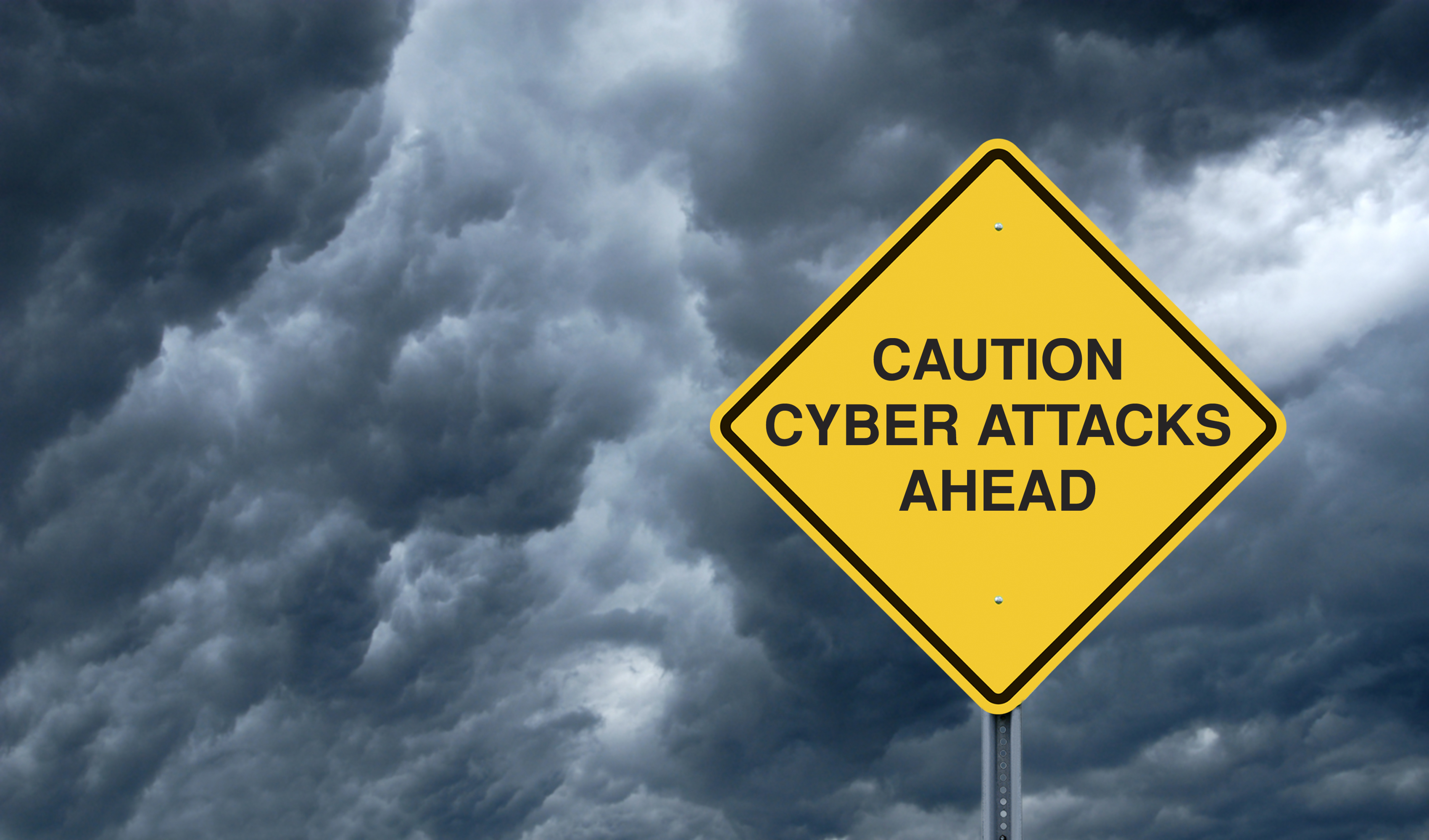 """A Caution Sign in Front of Storm Clouds Warning of """"Cyber Attacks Ahead."""""""