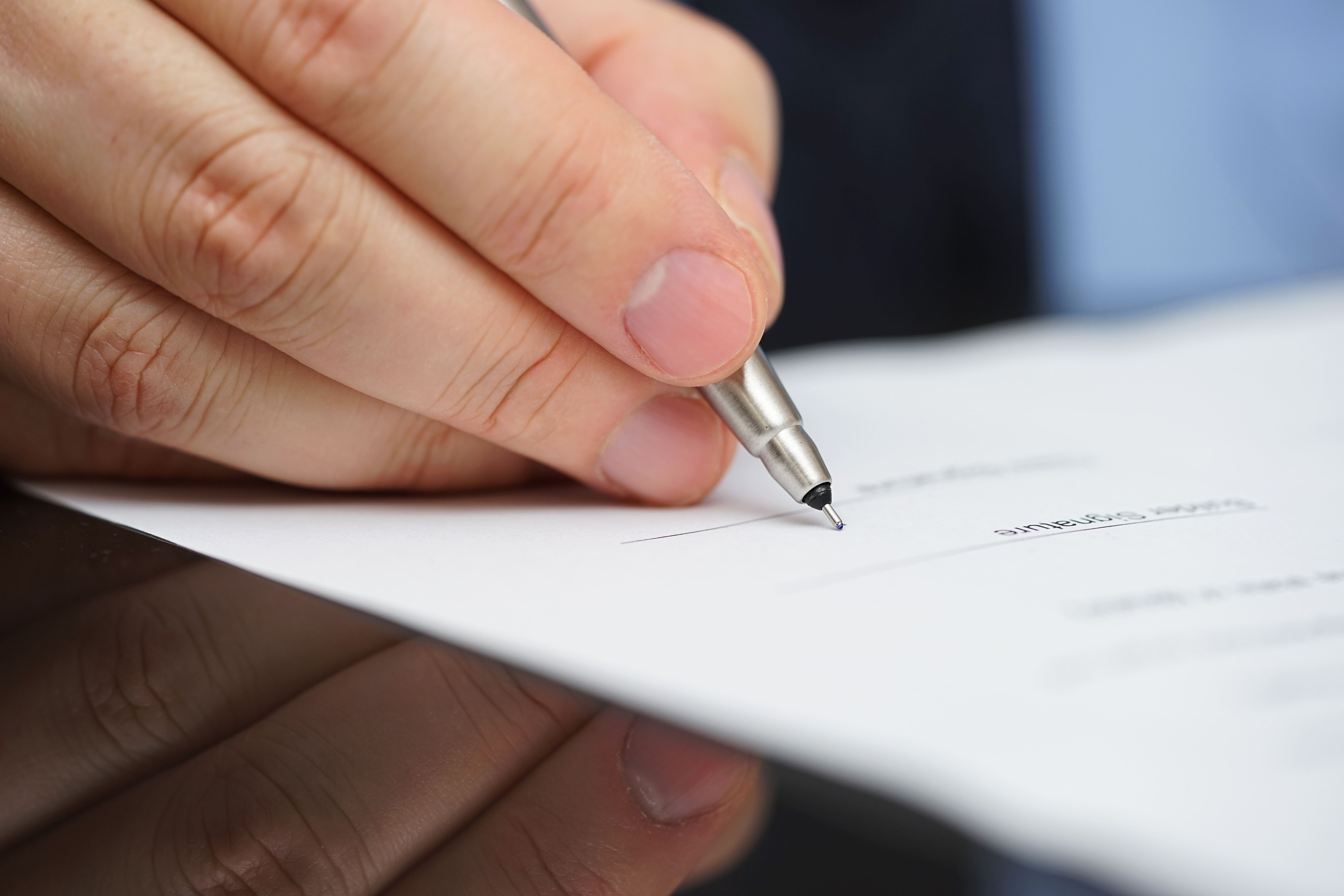 businessman in blue shirt and tie signing contract