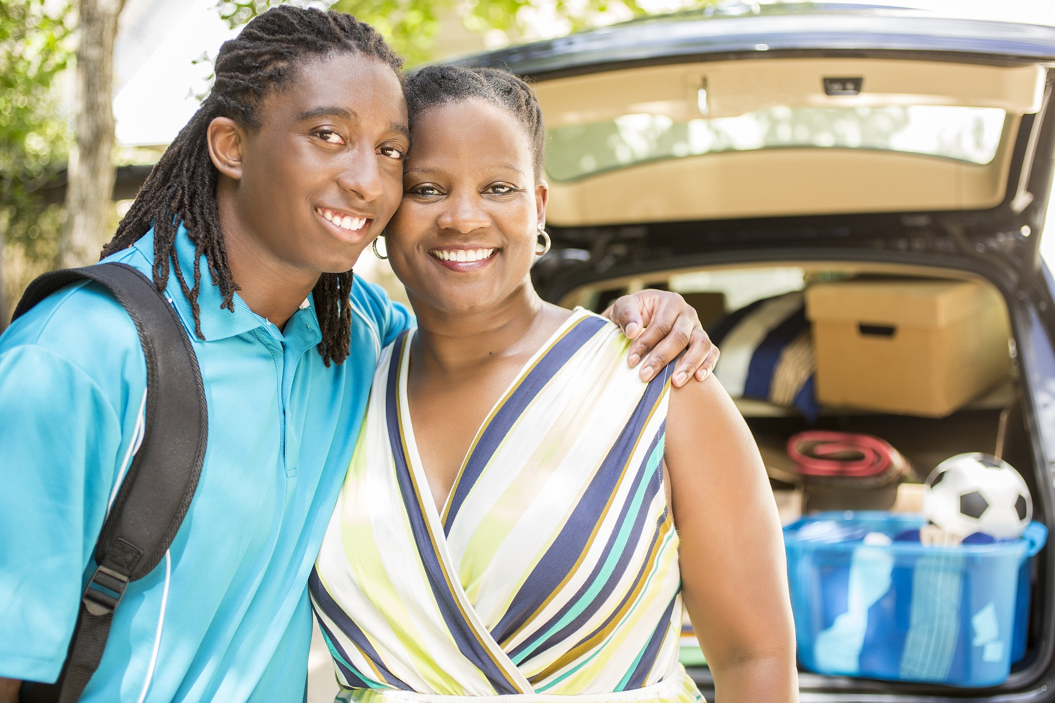 African descent boy heads off to college or moves away from home. The 18-year-olds' mother is helping him pack up his car as he gets ready for the big move. He is excited to start his college adventures and gives mom a big hug. He wears a backpack. Family events. Back to school.