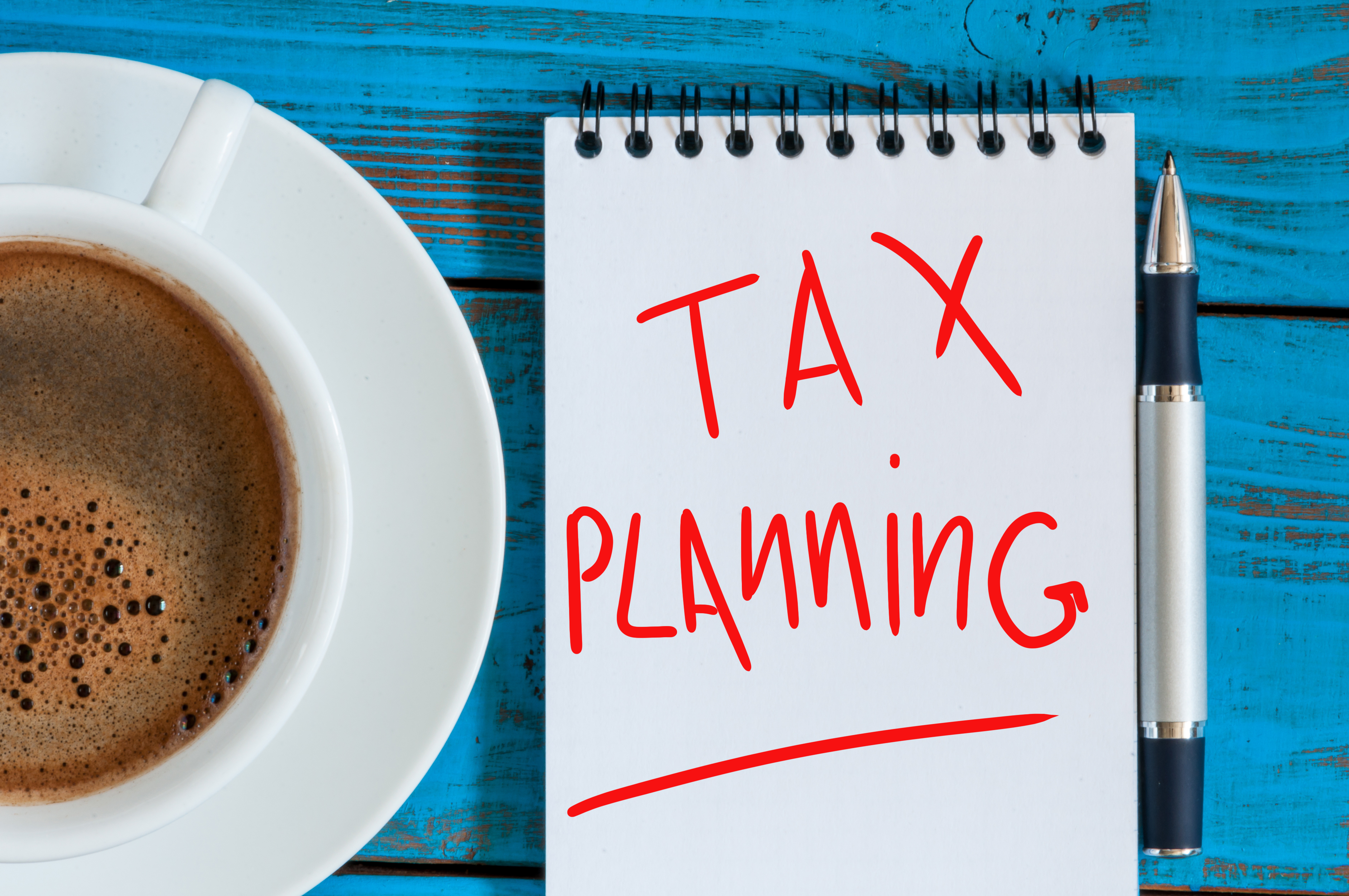 tax planning, reminder with red ink in the diary near morning coffee cup. top view.