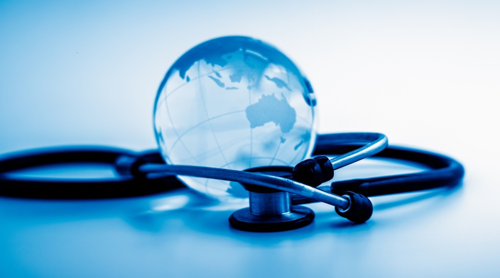 Global healthcare. Globe and stethoscope, studio shot.blue toned images.