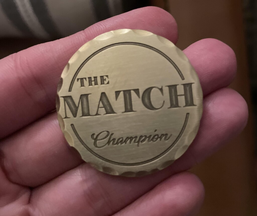 """The """"Champion"""" ball marker awarded to Kylie's team for winning The Match charity event."""